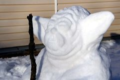 The head of an unusual snowman. Snowman of an unusual type with a staff. Reminds Yoda from movie Star Wars. You can use it for the article about Winter, winter royalty free stock photography