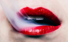 Head on view of a woman with vapor. Escaping her lips royalty free stock image