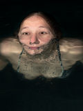 Head of a woman close up floating in water Stock Images