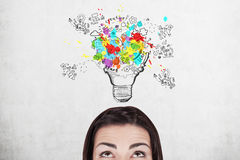 Head of woman and colorful light bulb Royalty Free Stock Photo