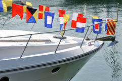Head of yacht and colorful flag. Yacht anchoring in harbor, with colorful flag decoration on head, shown as entertainment, yacht travel or maritime sport Stock Images