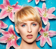 Head of a Young Blond Woman with Flowers on Sides Royalty Free Stock Image