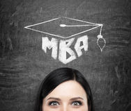 A head of young brunette lady who is thinking about MBA degree. Drawn a graduation hat on the black chalkboard background Stock Images