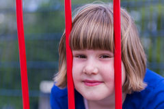 Head of young girl behind red metal bars Stock Photo