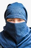 Head of young woman veiled with blue niqab scarf. Isolated on white Royalty Free Stock Photography