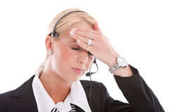 Headache. Receptionist with headset having a headache and reaching for her forehead Royalty Free Stock Photography