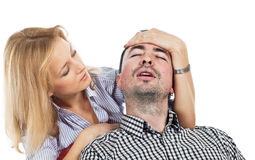 Headache. Anxious pretty young blond woman holding her hand on the forehead of his boyfriend suffering from headache Stock Photos