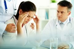 Headache. Portrait of women with headache touching her temples with medical staff near by Royalty Free Stock Image