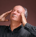 Headache. Portrait of a senior man suffering from a bad headache on a brown background Royalty Free Stock Images