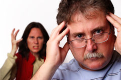 Headache. A man holding his head in the foreground while a woman gestures angrily behind him Stock Photo