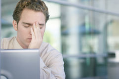 Headache. One young business man with head in hands with laptop in front Stock Photo