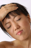Headache. Young chinese girl with headache royalty free stock photo