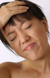 Headache. Young chinese girl with headache royalty free stock image