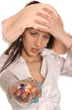 Headache. Young woman have a bad headache and holding pills, focus on pills stock photography