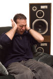 Headache. Man has a headache from listening to loud music Royalty Free Stock Photo