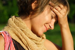 Headache. Young woman in the sun with a headache stock image
