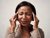 Headache. African american woman with headache migraine over gray background stock image