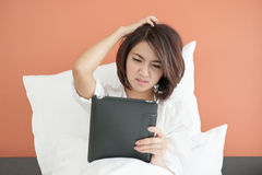 Headache Asian Young woman. Reading a E-magazine on bed Stock Image