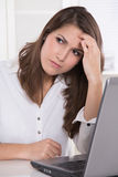 Headache: businesswoman scratching forehead with laptop Stock Images
