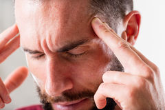 Headache or esp mind power. Man that seems to suffer a severe headache holding his head with hands or pointing with fingers, but he could have a powerful mind Royalty Free Stock Images