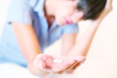 Headache girl with pills in hand Stock Photos