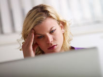 Headache and health problems for woman at work. Young beautiful caucasian blonde businesswoman working with laptop computer and having headache for stress Royalty Free Stock Image