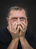 Headache. Man with face closed by hand Royalty Free Stock Image