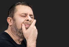 Headache. Man with face closed by hand Stock Images