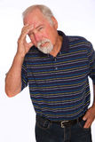 Headache. A mature man with a pained expression from a headache Royalty Free Stock Photo