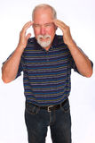 Headache. A mature man rubbing his temples for headache pain relief Stock Image