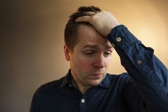 Headache or migraine, suffer from depression and loneliness. Caucasian man closes eyes with  palm. Headache or migraine, suffer from depression and loneliness Royalty Free Stock Photography