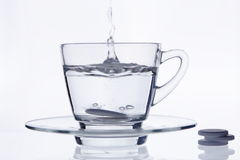 Headache pill. A headache pill falling into a cup of water Royalty Free Stock Images