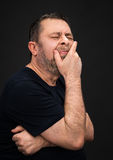 Headache. Man with face closed by hand Royalty Free Stock Images