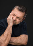 Headache. Man with face closed by hand Stock Photos