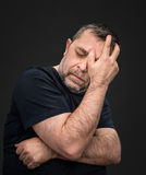 Headache. Man with face closed by hand Stock Image
