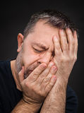 Headache. Man with face closed by hand Royalty Free Stock Photo