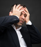 Headache. Man with face closed by hands Stock Image