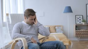 Headache, tense middle aged man sitting on casual chair stock footage