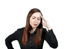Headache or thoughtfulness. Young woman on a white background has put a hand to her forehead and closed her eyes, expressing deep thoughtfulness or suffering Royalty Free Stock Photography