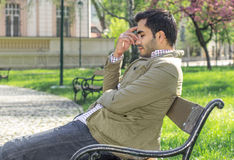 Headache, tiered man sitting in a park on bench stock photo