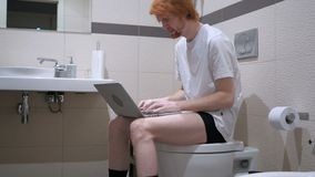 Headache, tired man using laptop in bathroom, commode. 4k, high quality stock video footage