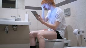 Headache, Tired Man Using Tablet in Bathroom, Commode. 4k , high quality stock video footage