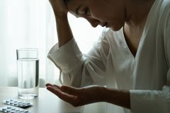 Headache women hand hold medicine with a glass of water, healthcare and medicine recovery concept. Headache woman hand hold medicine with a glass of water stock image