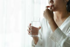 Headache women take medicine with a glass of water, healthcare and medicine recovery concept. Headache woman take medicine with a glass of water, healthcare and royalty free stock images