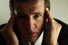 Headache from Work. A business man with a headache   Metaphorically, also a big problem Royalty Free Stock Photography