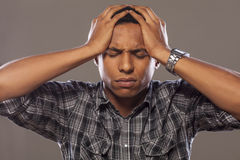 Headache. Young African American with a strong headache on grey background stock photos