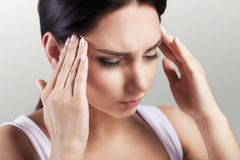 Headache in a young girl. Migraine. Fatigue after a hard working day. The concept of health. On a gray background. Headache in a young girl. Migraine. Fatigue Stock Images