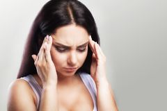 Headache in a young girl. Migraine. Fatigue after a hard working day. The concept of health. On a gray background. Headache in a young girl. Migraine. Fatigue Royalty Free Stock Photo