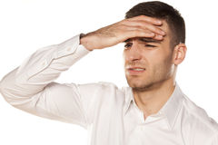 Headache. Young man with headache on white background stock photography