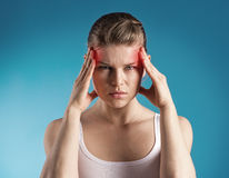 Headache. Young woman suffer from dizziness or vertigo holding her head. Portrait of exhausted female with migraine problem over blue background Royalty Free Stock Photography